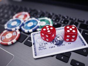 Würfel, Jetons und eine Kreditkarte auf der Tastatur eines Laptops